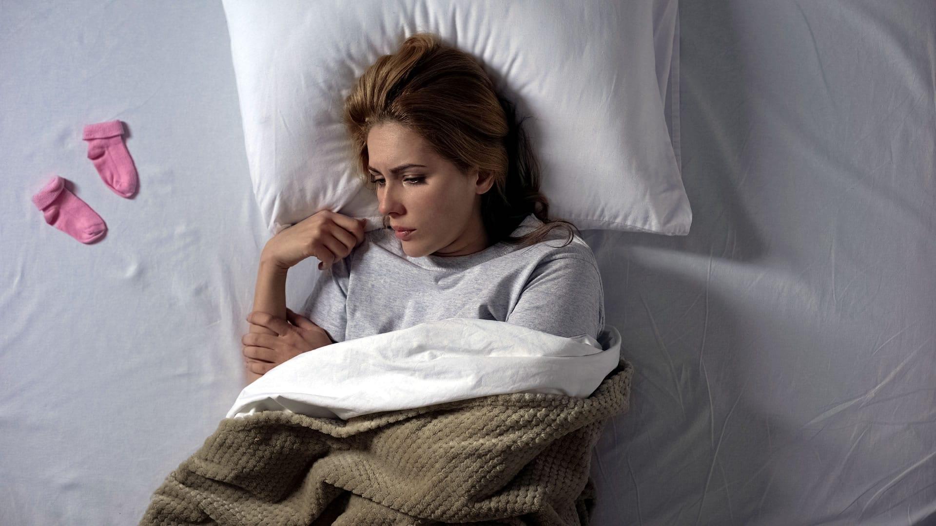 Mulher infeliz deitada em sua cama na expectativa de ter um bebê.
